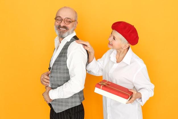Charmante kurzhaarige frau mittleren alters in der roten haube, die eine schachtel schokolade hält, die ihrem hübschen fröhlichen ehemann geburtstagsgeschenk gibt Kostenlose Fotos