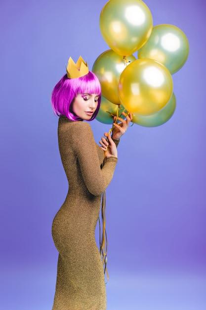 Charmante schöne junge frau im attraktiven modischen kleid mit fliegenden goldenen luftballons. rosa lila haarschnitt, krone, fröhliche gefühle, geschlossene augen, feier. Kostenlose Fotos