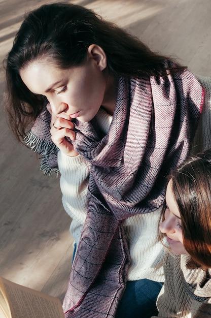 Charmante studentin freundinnen sitzen über ein buch Premium Fotos