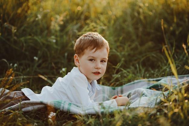 Charmanter kleiner junge liegt auf dem grünen rasen und genießt schön Kostenlose Fotos