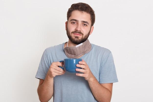Charmanter magnetischer hübscher junger bärtiger mann, der tasse mit tee am morgen hält und friedlichen gesichtsausdruck hat Kostenlose Fotos