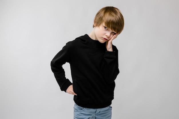 Charmanter teenager mit blonden haaren und dunklen augen. der teenager stützte seine wange mit den fingern ab. der teenager ist unzufrieden Premium Fotos
