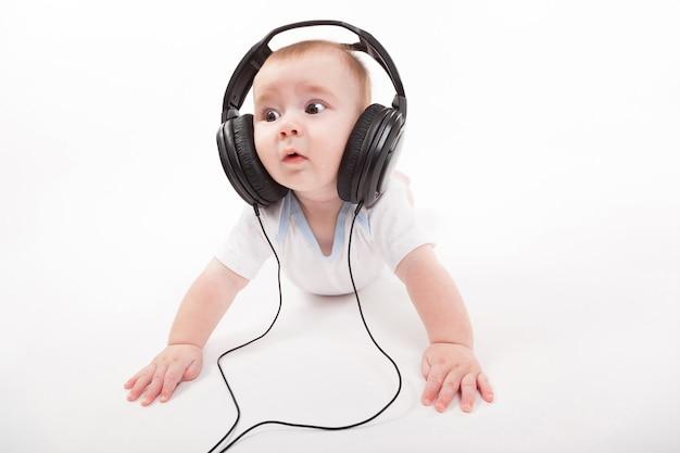 Charmantes baby mit kopfhörern zu hören Premium Fotos