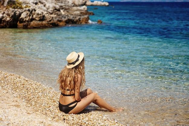 Charmantes blondes mädchen im schwarzen bikini beim sonnenbaden am strand Premium Fotos