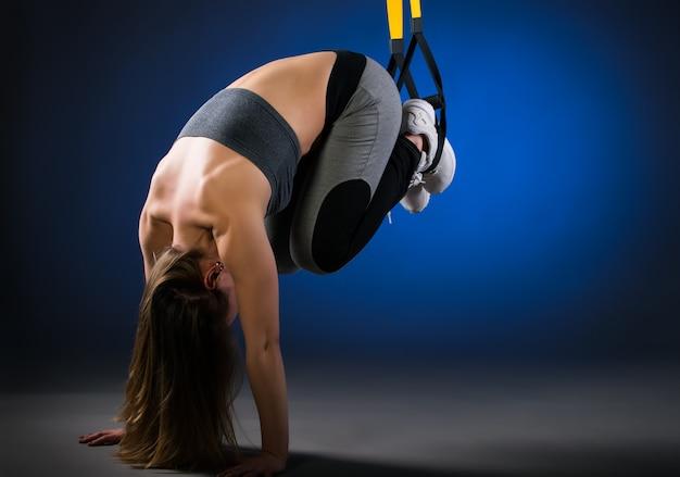 Charmantes junges langhaariges positives fitness-model, das mit hilfe von aufhängebändern liegestütze vom boden macht Premium Fotos