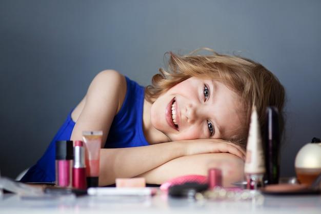 Charmantes kind, kleine schönheit, süßes mädchen von 7-8 jahren mit schönen blonden locken, make-up, mamas make-up am tisch, graue wand Premium Fotos