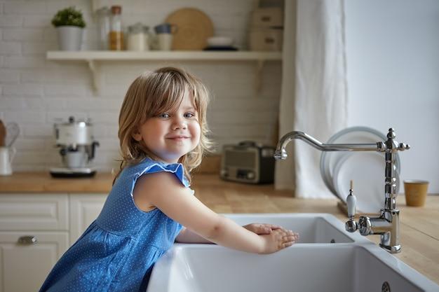 Charmantes kleines mädchen im blauen kleid, das hände in der küche wäscht. nettes weibliches kind, das kamera betrachtet und lächelt, mutter hilft, abwasch macht, am waschbecken steht. kinder, kindheit, kochen und hausarbeit Kostenlose Fotos