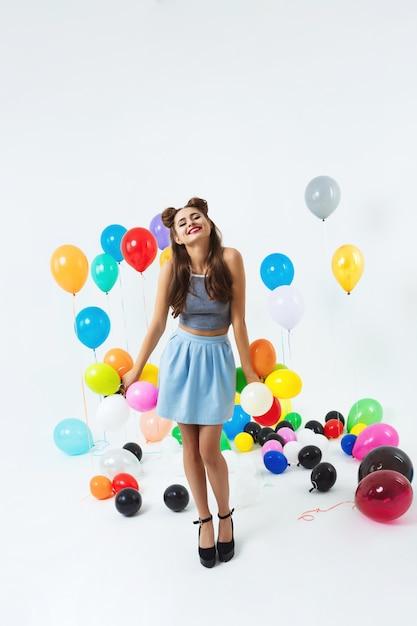 Charmantes mädchen im modeblick, der mit kleinen luftballons aufwirft Kostenlose Fotos