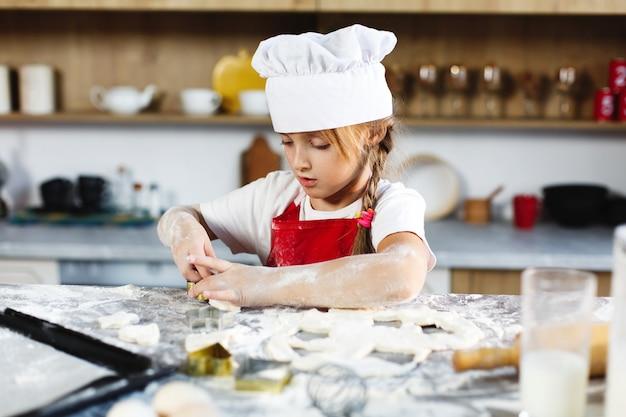 Charmantes mädchen macht spaß, kekse aus einem teig in einer gemütlichen küche zu machen Kostenlose Fotos