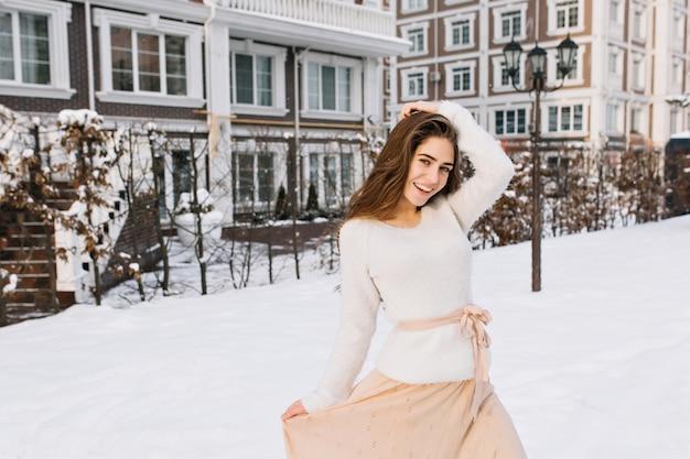 Charmantes weibliches modell im pullover und im rosa rock, die im wintermorgen im hof tanzen. foto im freien der herrlichen frau, die ersten schnee im dezember tag genießt. Kostenlose Fotos