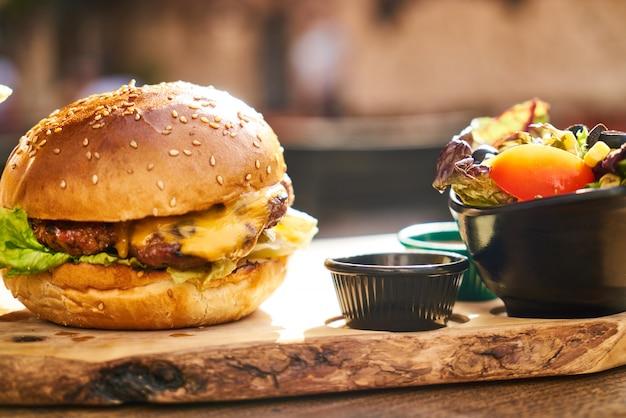 Cheeseburger mit pommes-frites auf dem holztisch Premium Fotos