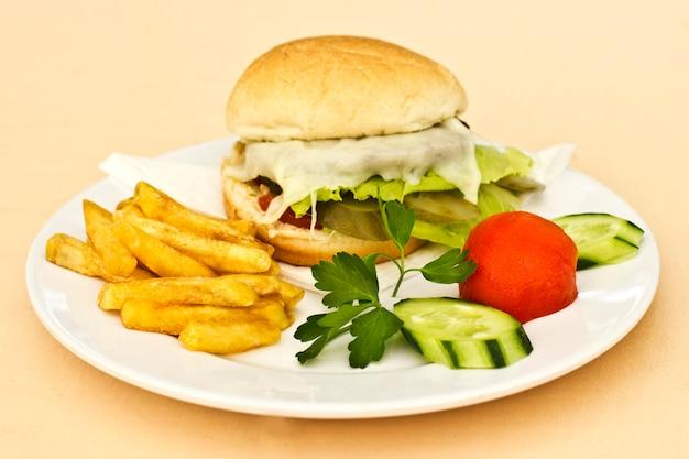 Cheeseburger mit pommes frites, gurkenscheiben und tomaten Premium Fotos