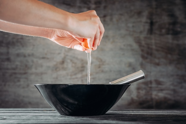 Chef bricht eier in schwarze schüssel auf holztisch Premium Fotos