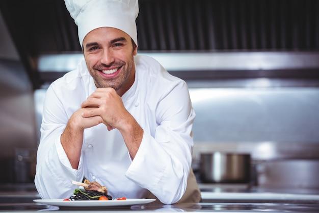 Chef, der auf der theke mit einem teller sich lehnt Premium Fotos