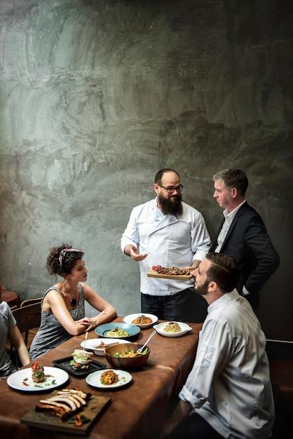 Chef, der den kunden im restaurant lebensmittel präsentiert Premium Fotos