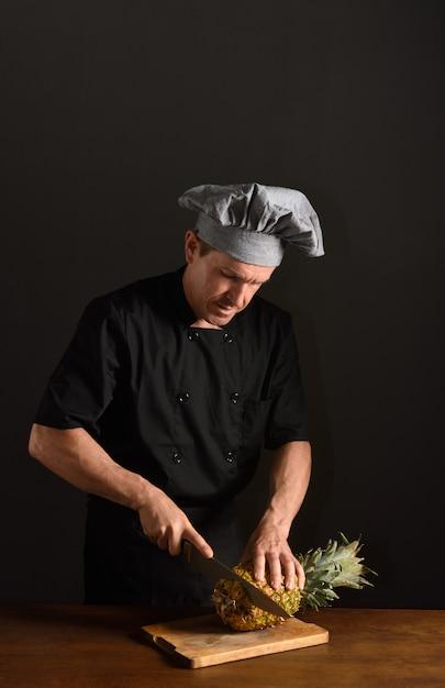 Chef, der eine ananas schneidet Premium Fotos