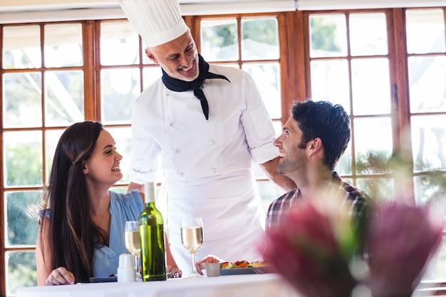 Chef, der mit paaren am restaurant spricht Premium Fotos