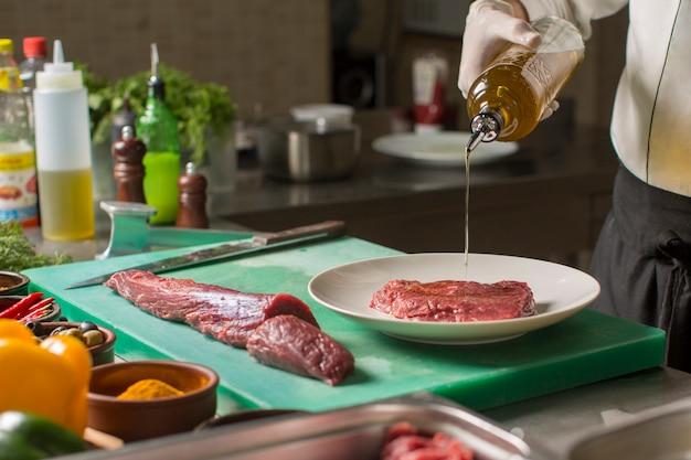 Chef, der olivenöl von der flasche auf steakstück in der platte gießt Kostenlose Fotos