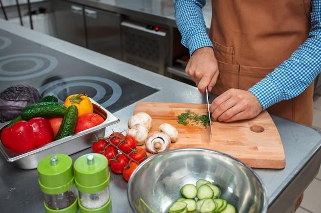 Chef in der braunen schürze kochend in einer restaurantküche Premium Fotos