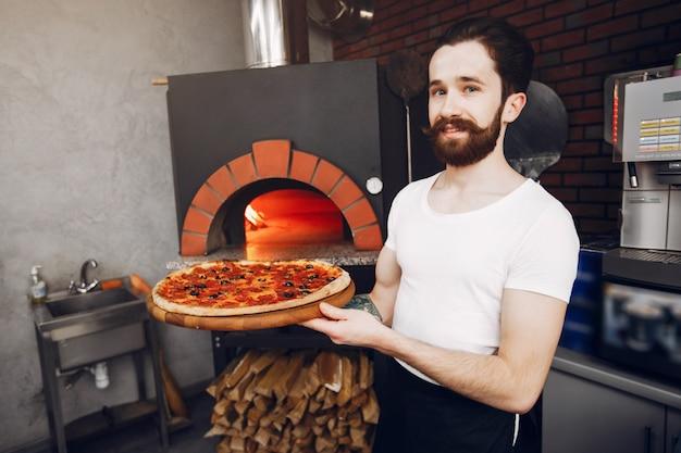 Chef in der küche bereitet pizza zu Kostenlose Fotos