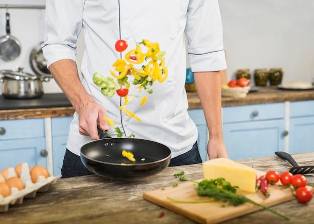 Chef in der küche kochend mit gemüse Kostenlose Fotos