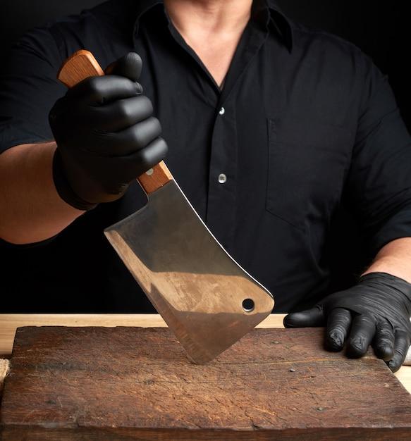 Chef in einem schwarzen hemd und schwarzen latexhandschuhen hält ein großes küchenmesser Premium Fotos