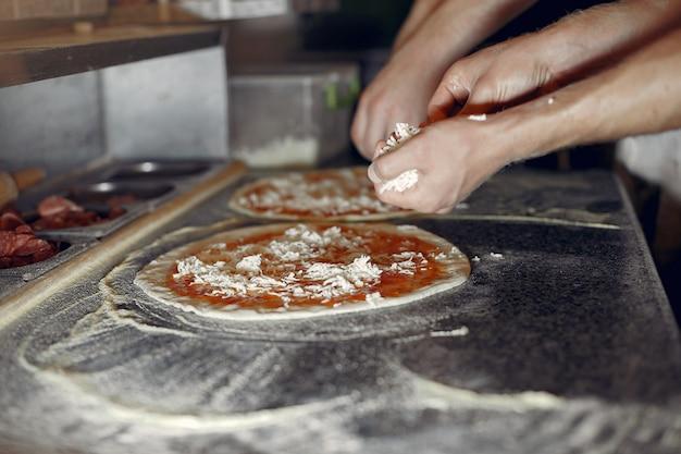 Chef in einer weißen uniform bereiten eine pizza zu Kostenlose Fotos
