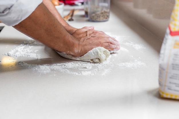 Chef knetet frischen teig zum backen von brot, pasta oder pizza. Premium Fotos