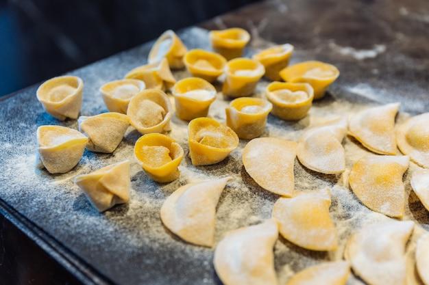 Chef macht kreisform-ravioli, indem er salbei und butter auf nudelteig füllt. Premium Fotos
