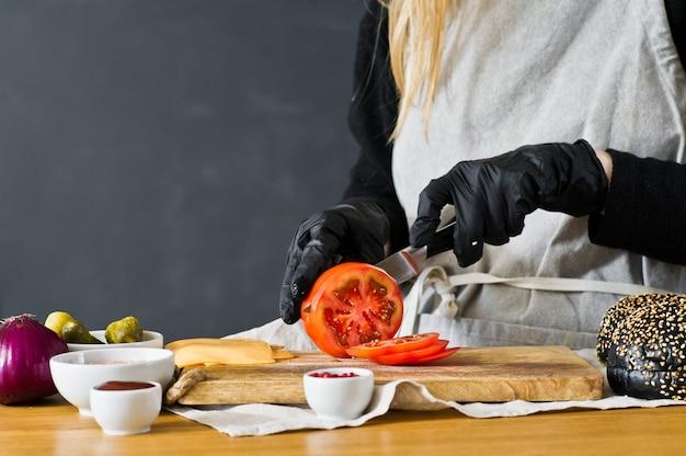 Chef schneidet rote tomaten. das konzept, einen schwarzen burger zu kochen. Premium Fotos