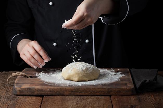 Chefhände, die mehlpulver auf rohen teig gießen. Premium Fotos