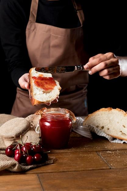 Chefkoch, der kirschmarmelade auf brot verteilt Kostenlose Fotos