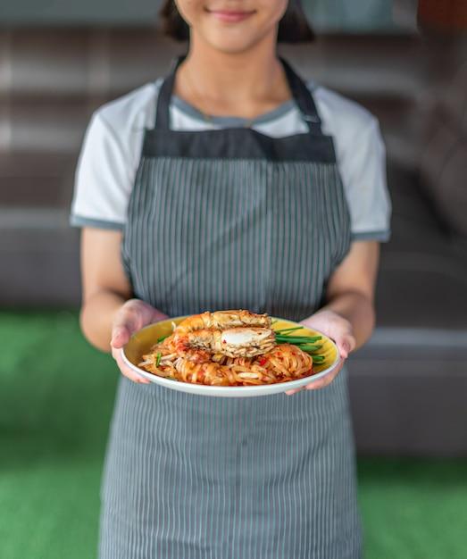 Chefkoch hält gebratene nudeln mit garnelen Premium Fotos