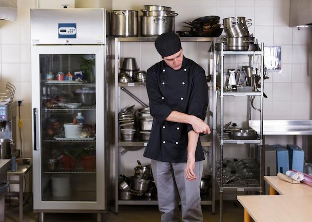 Chefkoch mit uniform und küchenutensilien Kostenlose Fotos