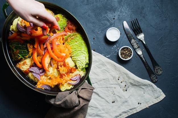 Chefkoch streut zwiebel auf mit fleisch und gemüse gefüllte wirsingrouladen. Premium Fotos