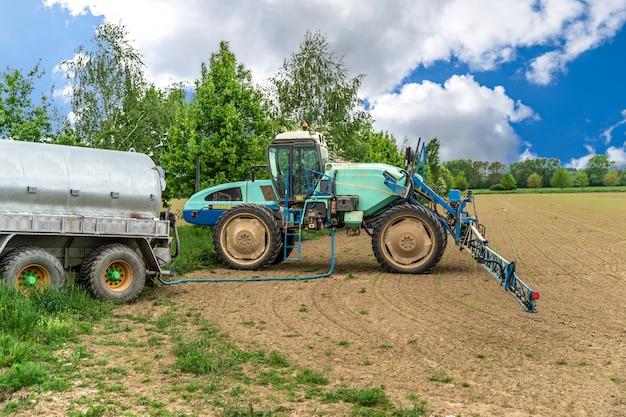Chemikalien gegen unkraut, die im tank eines traktors mit einem sprühgerät betankt werden Premium Fotos