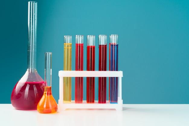 Chemische laborglaswaren mit verschiedenen farbigen flüssigkeiten auf tabelle Premium Fotos