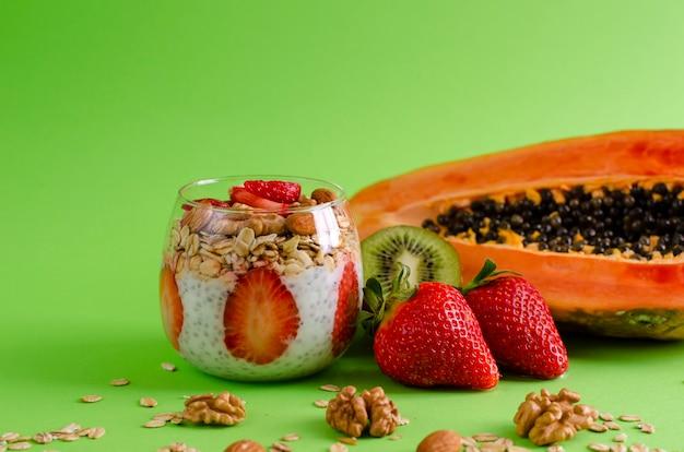 Chia-pudding mit frischen rohen tropischen früchten mit haferflocken und nüssen für die gesunde ernährung auf grün Premium Fotos