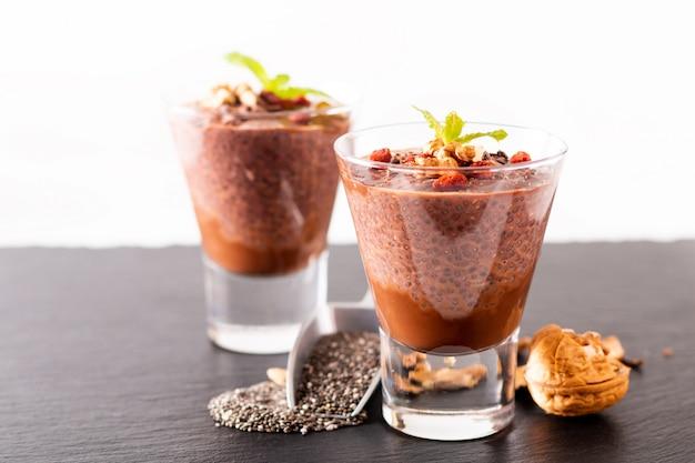 Chia-samen des gesunden lebensmittelkonzeptes, schokoladenmilchpudding mit goji und getrocknete walnüsse im kleinen glas auf schwarzem schieferbretthintergrund Premium Fotos