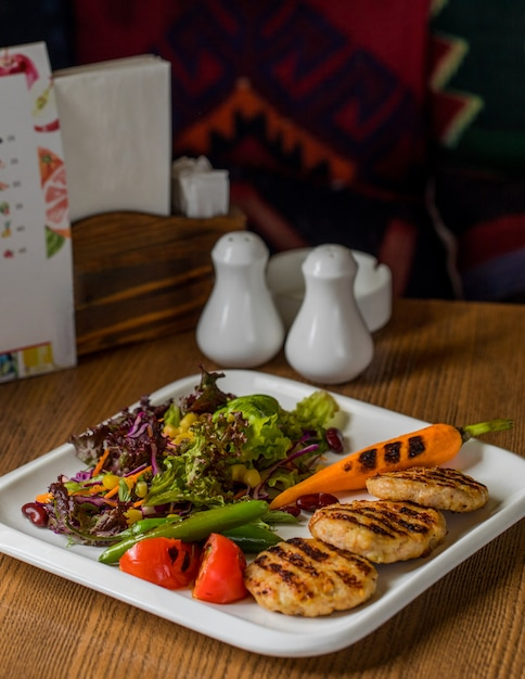 Chicken cotlets mit gegrillter karotte und grünem salat. Kostenlose Fotos