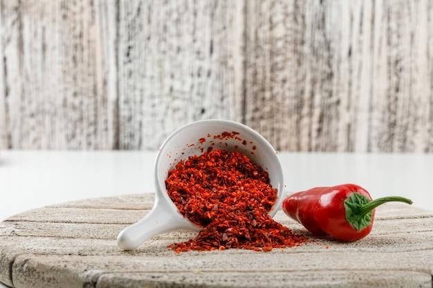 Chilipulver mit rotem pfeffer und holzstück in einer weißen schaufel auf weißer und hölzerner schmutzwand, seitenansicht. Kostenlose Fotos