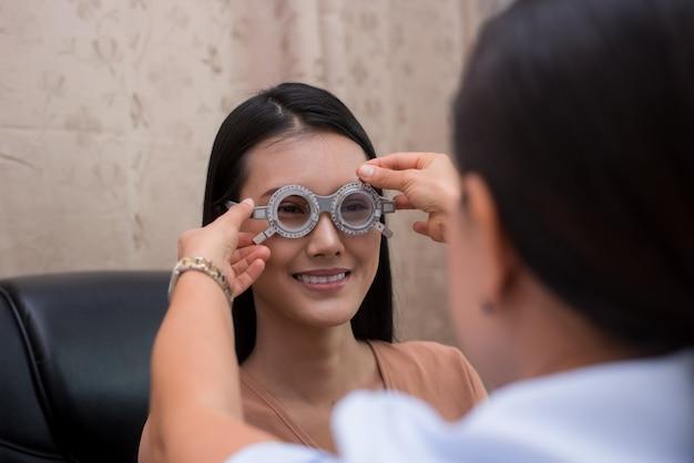 Chinesinnen, die augenuntersuchung an einem optischen shop tun. konsultation eines augenarztes. Premium Fotos