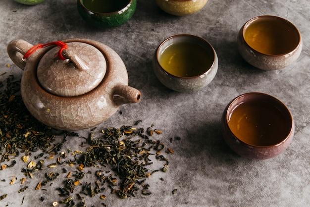 Chinesische braune teekanne und teetassen mit teekräutern auf konkretem hintergrund Kostenlose Fotos