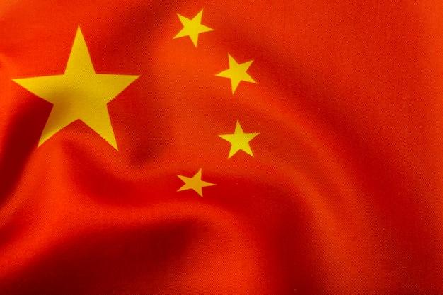 Chinesische flagge. flagge der volksrepublik china mit gelben sternen auf rotem grund. chinesische flagge mit seidenfalten im wind und einer textil- und stoffstruktur Premium Fotos