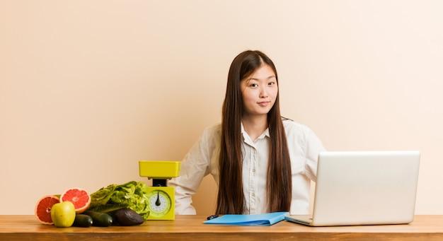 Chinesische frau des jungen ernährungswissenschaftlers, die mit ihrem laptop schilt jemand arbeitet, das sehr verärgert ist. Premium Fotos