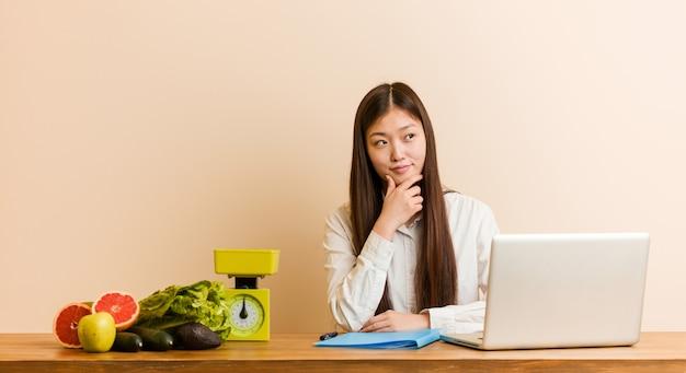 Chinesische frau des jungen ernährungswissenschaftlers, die mit ihrem laptop seitlich schaut mit zweifelhaftem und skeptischem ausdruck arbeitet. Premium Fotos