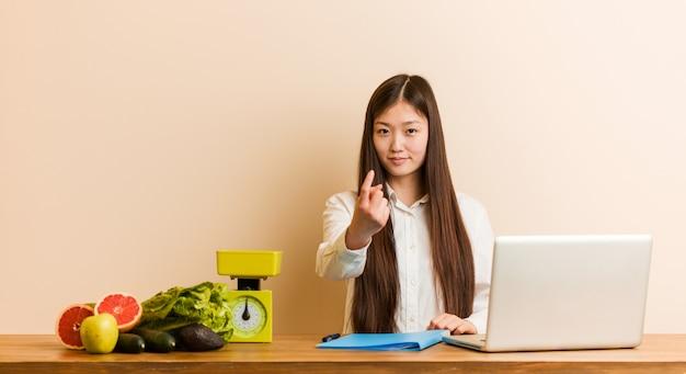 Chinesische frau des jungen ernährungswissenschaftlers, die mit ihrem laptop zeigt mit dem finger auf sie arbeitet, als ob einladung näher kommen. Premium Fotos