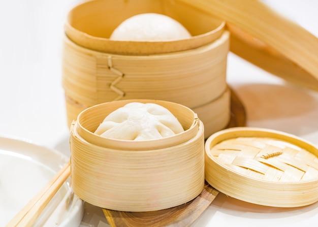 Chinesische knödel gedämpfte brötchen, gedämpftes brötchen in holzkorb serviert Premium Fotos