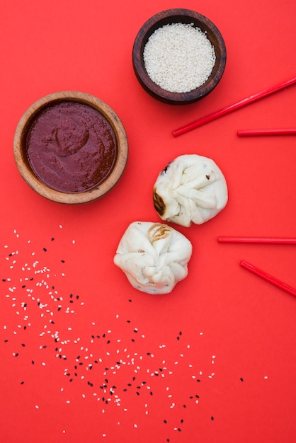 Chinesische mehlklöße mit soßen zum abendessen mit schüssel sesam und essstäbchen gegen roten hintergrund Kostenlose Fotos