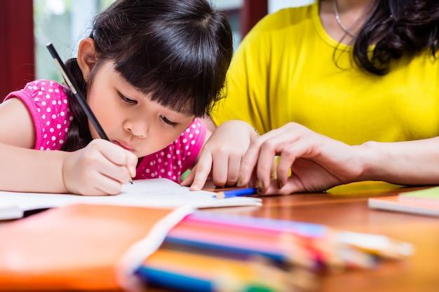 Chinesische mutter, die ihr kind homeschooling ist Premium Fotos